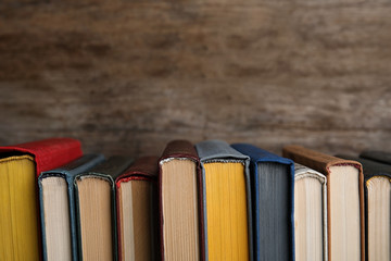 Stack of hardcover books on wooden background. Space for text