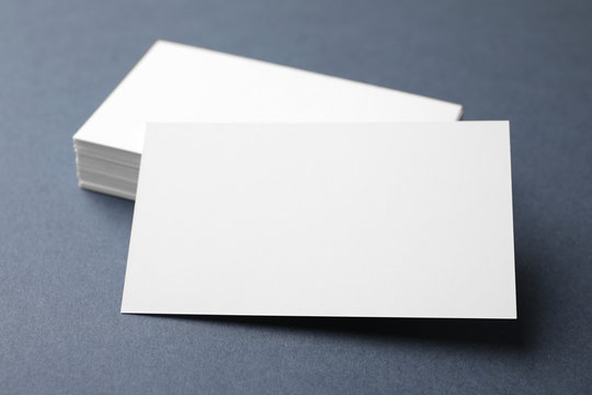Blank business cards on dark grey background, closeup. Mock up for design