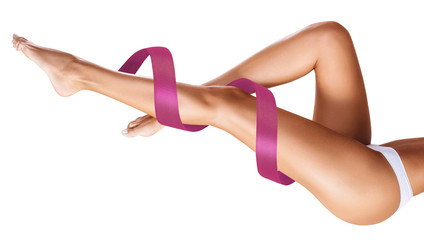 Women's legs with pink ribbon. Physical rehabilitation concept.