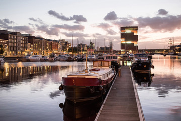 Zelfklevend Fotobehang Antwerpen Antwerpen, Belgium, beautiful night view of modern Eilandje area and port. Small island district and sailing marine at sunset. Popular travel destination and tourist attraction
