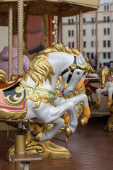 Horse carousel close-up. The head of a toy horse with a golden mane. Christmas scenery