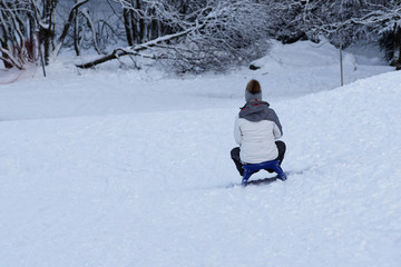 Young woman sledding on a sled by a toboggan run