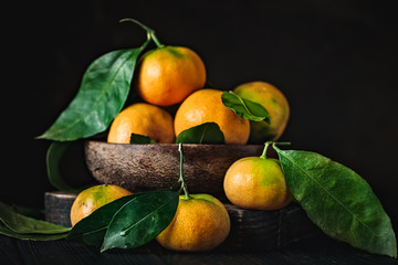 Tangerines with leaves on an old fashioned country table. Selective focus. Horizontal.