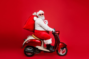 Profile side view portrait of nice bearded cheerful funny funky Santa father riding moped hurry up...