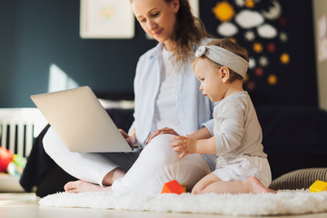 Young mother working remotely in social media marketing while taking care of children. Education for women,kids.Woman and daughter