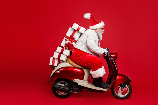 Profile side view portrait of nice bearded funny funky purposeful Santa Claus riding moped hurry up delivering pile stack shop purchases isolated on bright vivid shine vibrant red color background