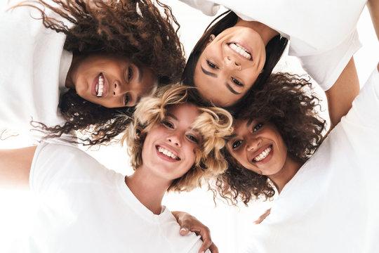 Women multiracial friends looking at camera.