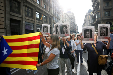 People holding an Estelada and pictures of Catalan politicians as they walk through Via Laetana Avenue during a protest after a verdict in a trial over a banned independence referendum, in Barcelona
