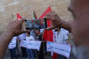 Palestinian man uses his mobile phone to take pictures of demonstrators taking part in a rally in support of Turkey's military action in northeastern Syria, in the southern Gaza Strip