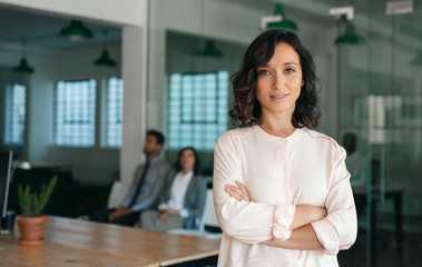 Smiling young businesswoman standing confidently in a large office