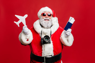 Portrait of funny hipster santa claus have journey abroad in terminal want travel take photo photigraphing wear spectacles eyewear eyeglasses costume isolated over red background