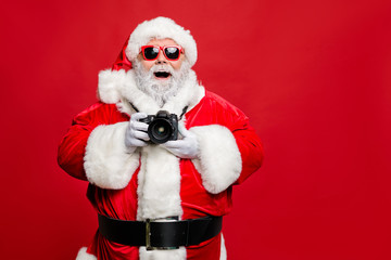 Portrait of excited enthusiastic santa claus in eyewear eyeglasses have voyage take photo wear stylish costume cap hat belt isolated over red background