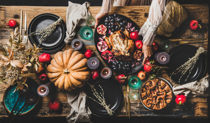 Thanksgiving party table setting for gathering. Flat-lay of roasted chicken, vegetables, fig pie, Autumn fruit, pumpkin, candles, tableware, silverware over rustic wooden table background, top view