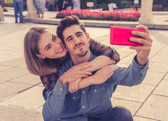Stylish tourist couple taking pictures selfie on smart phone on romantic trip around Europe