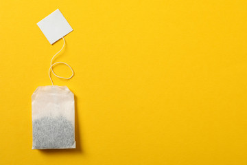 Tea bag with label on yellow background, space for text