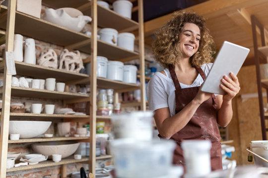 Craftswoman with tablet computer in art studio