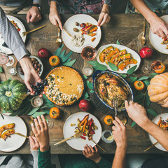 Thanksgiving, Friendsgiving holiday celebration. Flat-lay of friends eating meals at Thanksgiving Day table with turkey, pumpkin pie, roasted vegetables, fruit, rose wine, top view, square crop