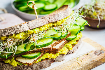 Big veggie sandwich with tofu, vegetables, sprouts and guacamole. Healthy vegan food concept.
