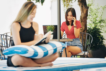Pretty young Vietnamese woman sitting at cafe table with opened laptop and calling coworker or client