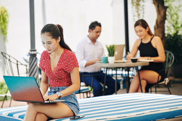 Pretty young Vietnamese woman sitting on edge of striped chaise-lounge and programming on laptop