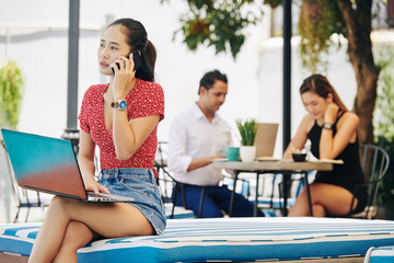 Pensive young Vietnamese woman sitting outdoors with laptop and talking on phone with coworker or client