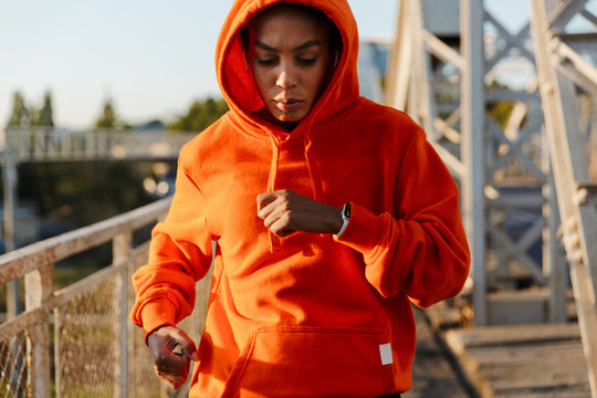 Photo of african american serious woman running while working out
