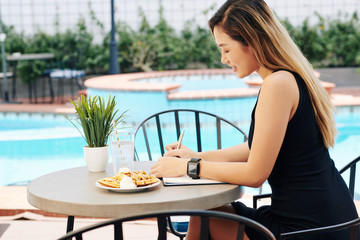 Young Asian woman sitting at table by swimming pool, eating breakfast and filling gratitude journal