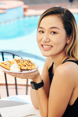 Young Vietnamese woman having sweet delicious Belgian waffles for breakfast in outdoor cafe