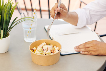 Hands of businessman eating healthy tasty chicken salad for lunch and filling planner