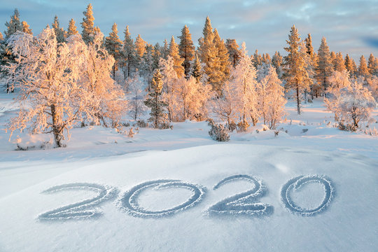 2020 written in the snow, mountain landscape in the background, holiday greeting card