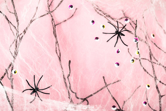 Pink halloween background with spider web, spiders and monster eyes