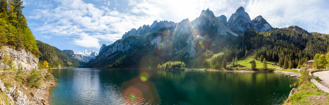 Famous Lake Gosau and Gosaukamm with Mount Dachstein. The sun is about to hide behind the high peaks while autumn is about to settle in with all the vibrant colors around the lake and hills.