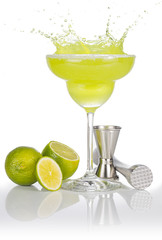Wall Mural - bartender tools and lime fruits around a splashing margarita glass