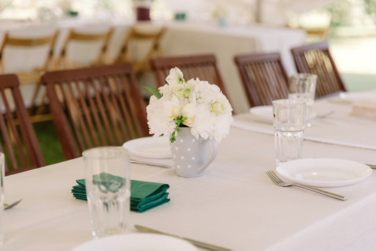 A miniature bouquet of white roses and chrysanthemums in a porcelain cup on the dinner table