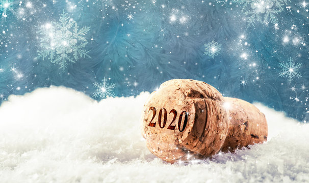 New Year or Christmas concept with champagne cork in snowdrift on blue background with snowflakes