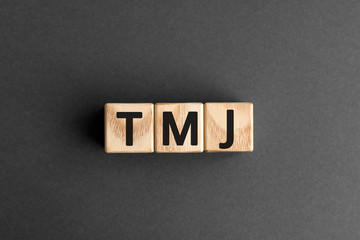TMJ - acronym from wooden blocks with letters, abbreviation TMJ temporomandibular joint syndrome, TMD Temporomandibular disorder concept, gray background