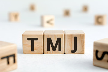 TMJ - acronym from wooden blocks with letters, abbreviation TMJ temporomandibular joint syndrome, TMD Temporomandibular disorder concept, random letters around, white  background