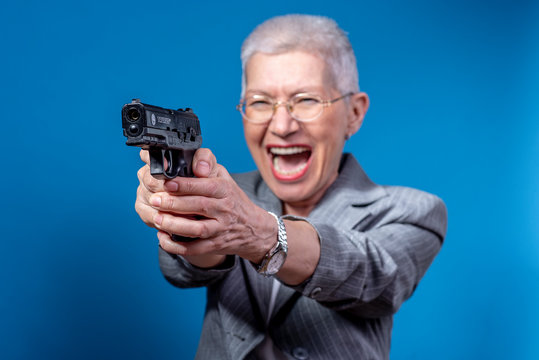 Old business lady shooting with her weapon, screaming