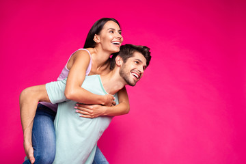 Photo of funny guy and lady holding piggyback spending free time looking far away wear casual clothes isolated vibrant vivid pink color background