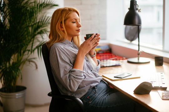 Young businesswoman drinking coffee in her office