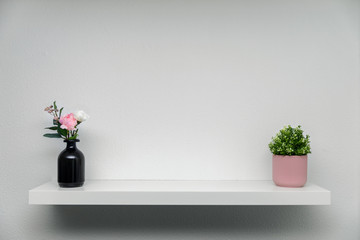 wooden shelf on white wall with green plant flower vase