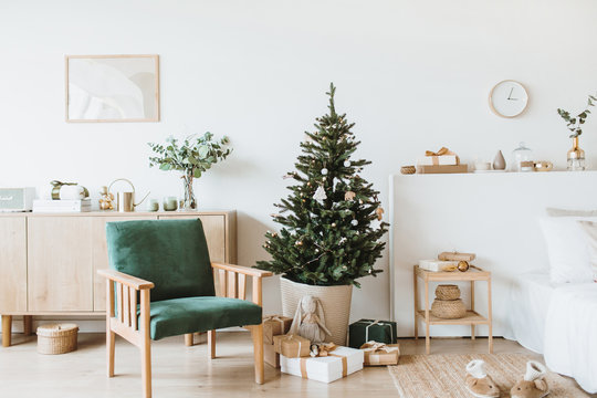 Modern interior design living room with Christmas / New Year decorations, toys, gifts, fir tree. Winter holidays composition.