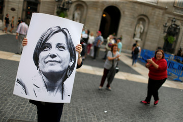 A woman holds a picture of Catalan politician Carme Forcadell during a protest after a verdict in a trial over a banned independence referendum, in Barcelona