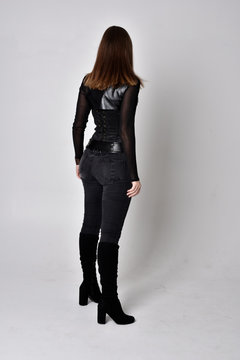 full length portrait of a pretty brunette woman wearing black leather fantasy costume with a dagger. standing pose, facing away from camera on a studio background.