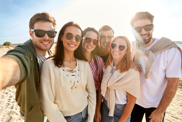 friendship, leisure and people concept - group of happy friends taking selfie on beach in summer