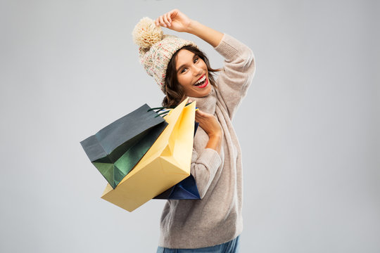 christmas, seasonal sale and consumerism concept - happy smiling young woman in knitted winter hat and sweater with shopping bags over grey background