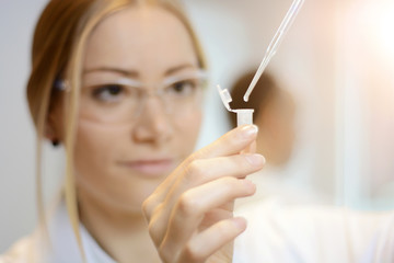 Woman as a scientist or doctor with reaction tube and pipette during examination and evaluation of sample