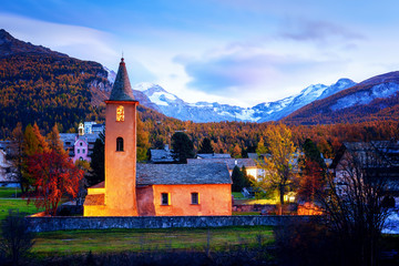 Old christianity church in Sils village (near lake Sils) in Swiss Alps. Red light on building and snowy mountains on background. Switzerland, Maloja region, Upper Engadine. Landscape photography