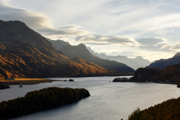 Aerial view on autumn lake Sils (Silsersee) in Swiss Alps mountains. Colorful forest with orange larch. Switzerland, Maloja region, Upper Engadine. Landscape photography