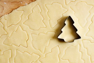 Cookie dough with Christmas tree shaped cutter, top view.